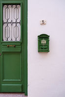 Green door and antique mailbox of a white traditional house in old Nicosia, Cyprus