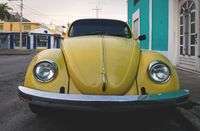 Old yellow Volkswagen beetle in the colonial streets of Merida, Yucatan, Mexico