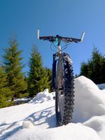 Wide view photo of mountain bike in deep snow. Winter mountains with road