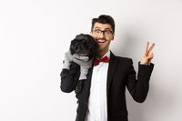 Cheerful young man in suit and glasses taking photo with cute black pug dog on his shoulder, smiling happy and showing peace sign, posing over white background