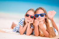 Little happy funny girls have a lot of fun at tropical beach playing together. Sunny day with rain in the sea