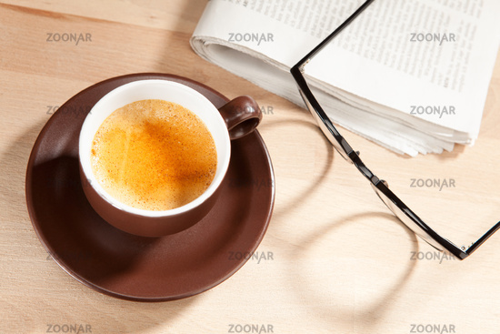 A cup of coffee with newspaper and glasses