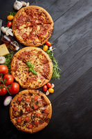 Freshly served, three various pizzas placed among tasty ingredients. Top view