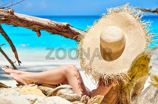 Woman sitting on beach at Seychelles