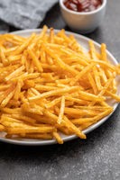 French fries. Fried mini potato sticks on plate.