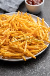 French fries. Fried mini potato sticks on plate.