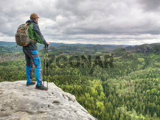 Man with a backpack and running shoes stands on top of a rock