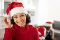 Portrait of woman in Santa hat smiling at home