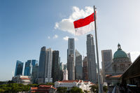 Singapore, National flag waves in front city skyline of central business district with skyscrapers