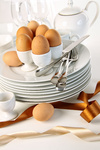 Eggs in white egg cups on a pile of plates with ribbons