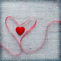 Red heart ribbon isolated on gray cloth background.