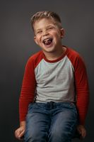 Facial expressions, emotions, feelings. Funny laughing boy in red shirt with eyes shut. Happy kid on dark grey background. Funny family time. Little boy enjoying having fun in studio