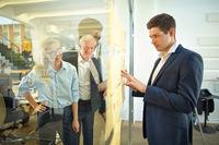 Mann schaut auf Notizen an Wand aus Glas