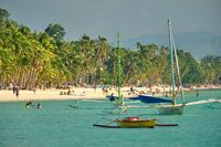 Boracay, Philippines - Jan 29, 2020: White beach of Boracay island. Tourists walk along the beach and swim in the sea. A few days before the outbreak of the coronavirus.