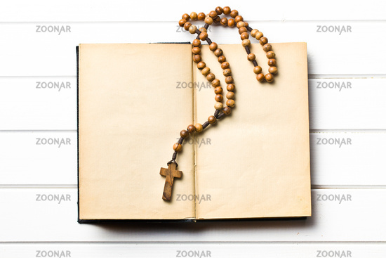 Wooden rosary beads with old book