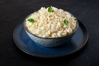 Cooked rice with fresh parsley leaves, in a bowl, on a dark background