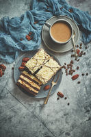 Tasty layered cake sprinkled with white chocolate. Served with cup of coffee on a gray concrete