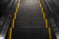Empty escalators stairway with a yellow stripes.