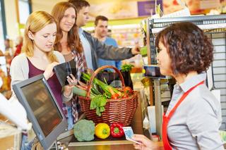 Frau an Kasse im Supermarkt fehlt Geld