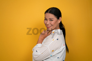 Charming Asian woman smiling at camera. Cute middle aged female model cutout on yellow background