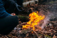 Man warms his hands on fire. Burning wood at evening in the forest. Campfire at touristic camp at nature. Barbeque and cooking outdoor fresh air. Flame and fire sparks on dark abstract background. Concept of safety and responsibility to nature
