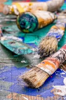 Brush, spatula and color pigments on a wooden palette