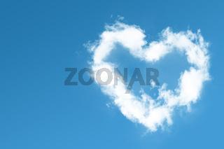 Fluffy heart cloud on blue sky