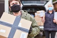 Paketbote mit Mundschutz bringt Lieferung zu Weihnachten