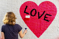 A young girl is painting a red heart and the black text LOVE on a white house wall