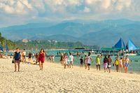 Boracay, Philippines - Jan 29, 2020: White beach of Boracay island. Tourists walk along the beach and swim in the sea. A few days before the outbreak of the coronavirus.