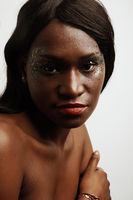 Beautiful african young woman posing over white wall. Vertical close-up.