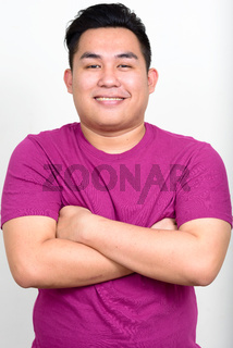 Portrait of happy young handsome overweight Asian man with arms crossed