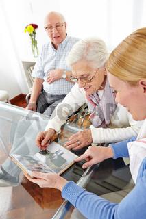 Seniorin schaut Fotoalbum an mit Tochter