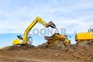 Excavator is loading a truck with ground on building site