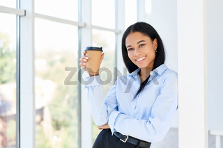 Happy black business woman with cup of coffee in hand during break time in modern office