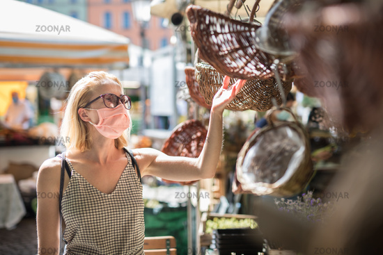 Casual woman shopping outdoor at open market stalls wearing fase masks for protection from corona virus pandemic in Munchen, Germany