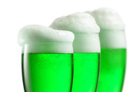 Fresh green beer with thick foam in the glasses.