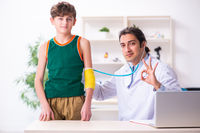 Sick boy visiting young male doctor pediatrician