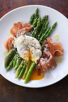 Eggs Benedict with parmesan, green asparagus and Parma ham.