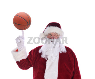 Santa Claus with his index finger pointing up with a basketball soccer ball balanced on the tip, isolated on white