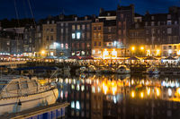 Harbor Honfleur at night with ships and restaurants, France