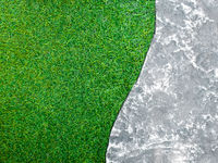 Surface texture of concrete walkway flooring beside the plastic artificial grass of lawn