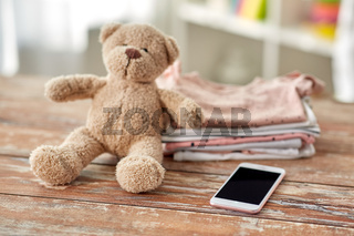 baby clothes, teddy bear toy and smartphone
