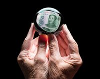 Hands holding a crystal glass forecasting ball reflecting the head on Chinese 50 Yuan bill
