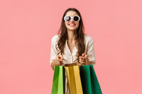 Woman went shopping, buying new clothes, special discounts for holiday season, standing with shop bags and smiling camera, wearing sunglasses, standing pink background excited
