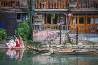 Women in front of old historic wooden Diaojiao houses in Fenghuang