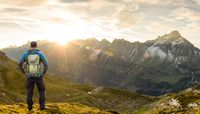 Hiker Man with Backpack enjoying amazing sunrise in the mountains with nice lens flares and sunbeams. Alps, Allgau, Bavaria, Tirol, Austria and Germany.