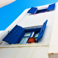 Windows with trditional blue shutters in Mykonos