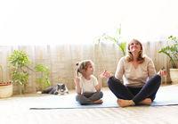 Grandmother and granddaughter meditating together