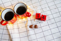 Two cups of coffee in red cups on a background of chocolate canfet in the form of a heart. Valentine's Day Morning Surprise.
